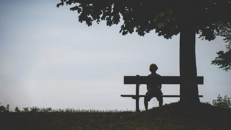 Criança sentada sozinha em um banco, embaixo de uma árvore.
