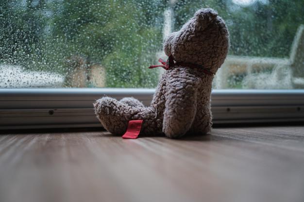 Urso de pelúcia no chão, posicionado como se olhasse pela janela molhada da chuva