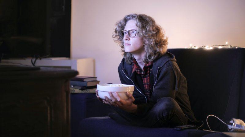 Pessoa sentada no sofá (aparentemente em frente a uma televisão, pela luminosidade) segurando um recipiente com pipoca.