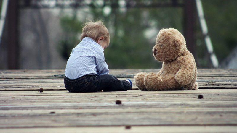 Criança pequena sentada em posição triste de fronte a um urso de pelúcia de mesmo tamanho e postura
