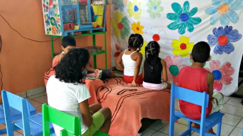 Crianças e adolescentes sentados de costa, olhando para a frente o que parece ser uma cortina improvisada com lençol para um teatro ou apresentação