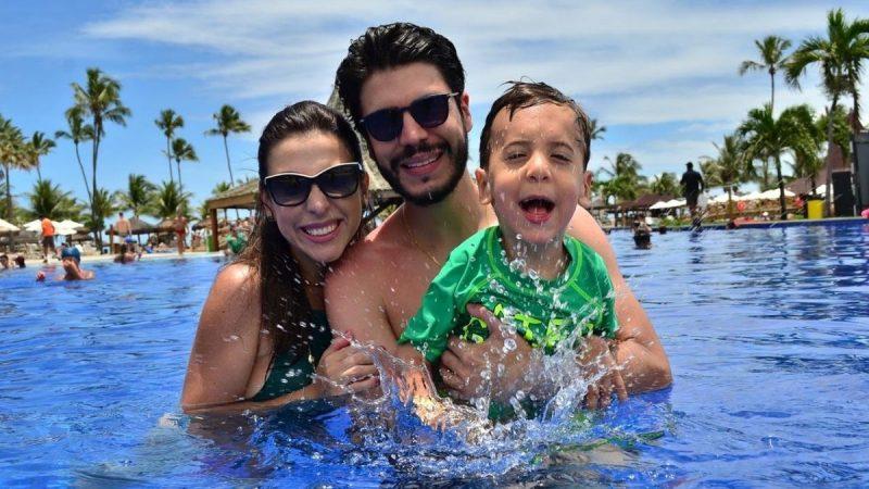 família - mãe, pai e menino em uma piscina
