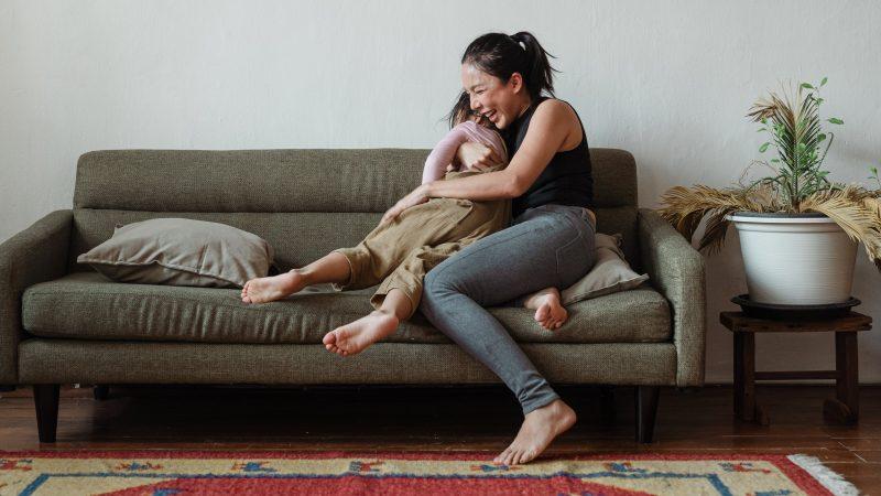 mãe e filha brincando no sofá