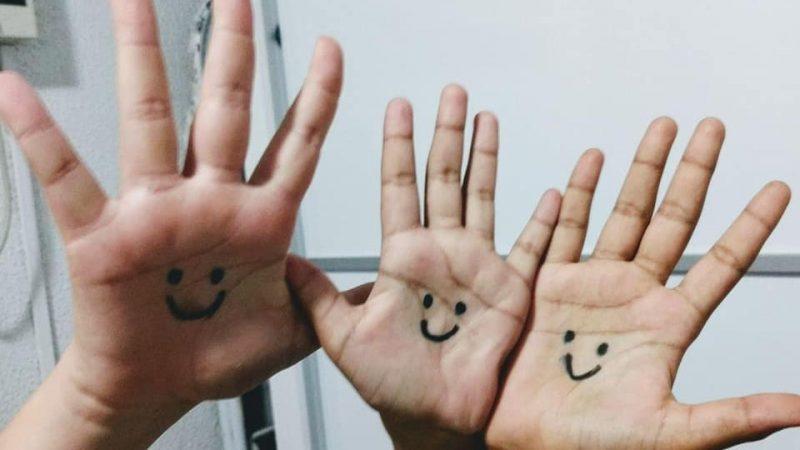 3 mãos pequenas com olhos e sorriso desenhados a caneta na palma