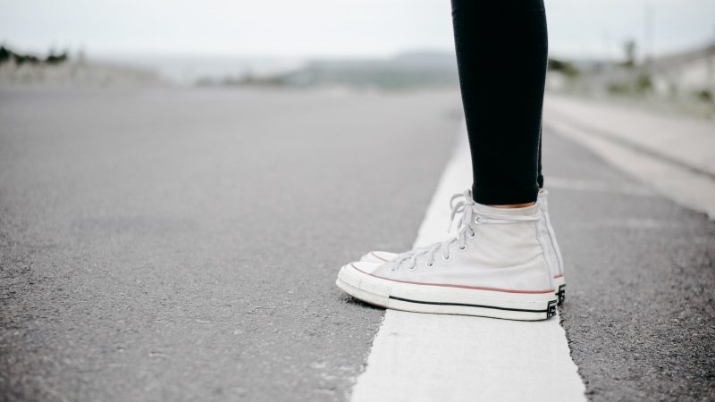 Pessoa parada em cima de uma linha pintada no chão.