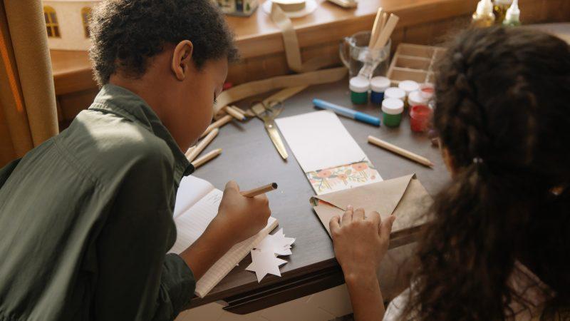 Duas crianças sentadas de costas fazendo atividades de artesanato